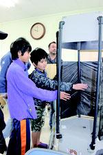 竜巻発生装置に触れる参加者ら=11日午前、石垣島地方気象台