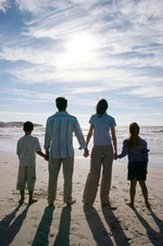 Husband and wife with children on a beach holding hands gazing at the morning sky, representing humanity redeemed.
