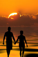 Lovers walking hand in hand along waters edge with the sun setting on the horizon