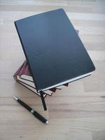 Bücherstapel und Notizbuch