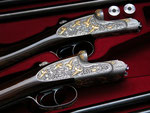 Intricate engraving with gold inlays on a pair of shotguns caliber 20/70 with a second set of barrels in 20/76.