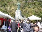 灯台の真下に当たる中岡慎太郎の像の前が「観光びらき」の会場。カツオのたたきを食べながらビールを楽しみにしていたが、12時半には全て売り切れ。飴湯のサービスも終わっていた。弁当だけはなんとか買えた。