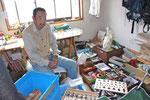 「メカムシ」デザイン工房代表の白石卓也さん。アトリエは作品や材料でいっぱい!