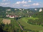 Zwei Triebzüge der Baureihe 611 fahren als RE 3214 nach Neustadt im Schwarzwald. Auf ihrem Weg liegen auch die mächtigen Klosteranlagen des Bendiktinerklosters Beuron. Gerade überqueren die Triebwagen die noch junge Donau (01.08.2014).