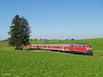 Auf dem Weg nach München befindet sich hier 218 492 mit RE 57511. Sie passiert hier einen unbeschrankten Bahnübergang bei Albatsried, während die Bauern das Sommerwetter eifrig nutzen und ihr Heu einfahren (20. August 2012). 14/35