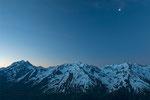 Ganz klein steht der Mond über den Bergen hinter mir