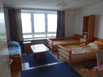 Großes Schlafzimmer mit 4 Betten (Schrank, Tisch, 1 Bett im Hintergrund)