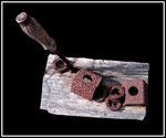 """Brennholzskulptur """"Werte III, WVZ Nachträge, aus 1996, Eisen, diverse Materialien und Farbe auf Brennholzscheid"""