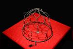 """Materialmontage """"Maulkorb"""", ca. 1994, im Werkverzeichnis """"Nachträge"""", Materialmontage aus Drahtmaulkorb, 50-Pfennig-Stück auf rotem Tuch und Sockel"""