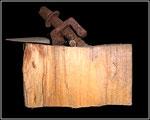 """Materialmontage """"ohne Titel - mit Sicherung"""" WVZ 1.002 / aus 7.96, Brennholz-Skulptur erinnernd an die Arbeiter bei Krupp und Thyssen, damals und heute / Metalle, Krampen, Sicherung, beschriebener Holzkeil auf Brennholzscheit / b 24,5 cm, h 20,0 cm"""
