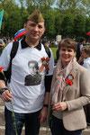 Mann und Frau mit dem Sankt-Georgs-Band, roter Nelke und auf dem T-Shirt das Foto eines Angehörigen der Roten Armee. Foto: Helga Karl am 9.Mai 2015