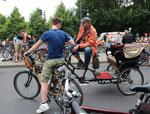 Zwei Radfahrer unterhalten sich, mit Fahrrad-Kutsche. Bei der Fahrrad Sternfahrt Berlin. Foto: Helga Karl