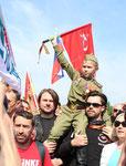 Junge Männer tragen einen Jungen in Armee-Uniform mit Orden auf der Schulter, der die Rote Fahne hoch hält. Foto: Helga Karl 9.Mai 2015 Sowj. Ehrenmal Berlin