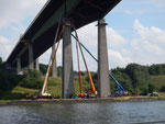 Vier Telekräne und vier - fünf Männer mit Blauhelmen unterschiedlicher Farbe montieren Stahlträger an einem Brückenpfeiler der Rader Hochbrücke