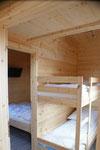 Etagenbett, hinten das Schlafzimmer mit französischem Bett