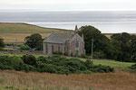 Kirche am Rand einer kleinen Ortschaft.