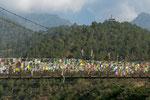 Die Hängebrücke ist mit zahlreichen Gebetsfahnen in fünf Farben geschmückt.