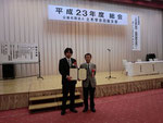 表彰状を授与されて喜ぶ岡林理事と右城会長