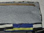 Typ XX: Die Ordensbänder sind quadratisch teilweise übereinander gelegt und über der Blechplatte vernäht. Die Rückenabdeckung besteht aus einem gräulichen Filzstoff. Typische Anfertigung der 1930/40er Jahre; möglicherweise von Eck, Frankfurt/Main.