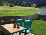 Aussenbereich mit Gartentisch und Stühlen, Sonnenschirm