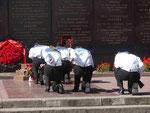 Jugendliche knien vor einem Kriegerdenkmal in Sewastopol/ Ukraine