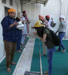 Freiwillige teilen heiliges Wasser aus in einem Sikhtempel in Delhi