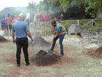 Restaurantmitarbeiter graben eunen Essenskübel auf dem Vulkanofen auf den Azoren aus