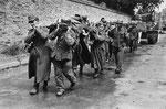 Deutsche Gefangene tragen verwundete Kameraden aus Cherboug heraus