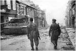 Nach dem Ende der Kämpfe in Villers-Bocage: Zwei Panzergrenadier vor einem zerstörten Tiger