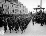 Soldaten des US VII Corps paradieren über den Rathausplatz in Cherbourg