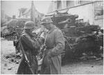 Nach dem Ende der Kämpfe in Villers-Bocage: zwei Panzergrenadiere vor einem zerstörten britischen Panzer des Typs Cromwll