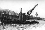 Der Dampf-Schwimmkran für die Rheinausbaggerung in Basel der Bauunternehmung Gebr. Meyer Köln, Kran 7 in Birsfelden, 1958 (Im Bild ganz rechts der Kranführer und Kapitän des Schwimmkrans)