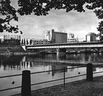 Die Dreirosenbrücke und der St.Johann-Hafen mit den Umschlagsunternehmen SILAG St.Johann Lagerhaus- & Schifffahrtsgesellschaft, ROBA, SPEDAG und mit den beiden Gaskesseln und der Chemiefirma «Durand& Huguenin» im Jahre 1958