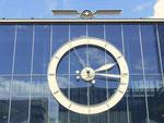 Das grosse Zifferblatt der Uhr an der Rundhofhalle der Mustermesse, zuoberst: das abstrakte MUBA-Signet
