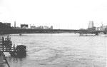 """Blick gegen die Johanniterbrücke und dem St.Johann-Hafen und der Dreirosenbrücke, ganz links das Feuerlöschboot """"St.Florian"""",1969"""