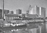 Die Umschlagsanlagen der BRAG (Basler Rheinschifffahrts Aktiengesellschaft) im Hafenbecken 2 im Jahre 1963, im Hintergrund die riesigen Gaskessel der Gaskokerei Basel. Foto aus einem alten Inserat der BRAG