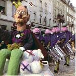 Die Fasnacht 1965 in der Clarastrasse, Tambourmajor einer Clique mit dem Sujet «Bundesrat Chaudet und der Mirage-Skandal und der Jura-Konflikt», die Trommler sind Schweizer-Militär-Ärsche.