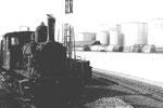 Eine Rheinhafen-Dampflokomotive vor den grossen BP-Tanklagern im Hafen Klybeck, 1971