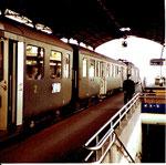 Ein Zug auf Gleis 10 im Bahnhof Basel SBB wartet auf das Abfahrtssignal des rot bekappten Bahnhofsvorstandes, 1980