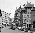 Die Spiegelgasse mit einem Tram der Linie 18, links der Spiegelhof (Polizeigebäude) und rechts das Restaurant «Meerkatz« und der ACV-Laden «Börse« (heute Coop), 1958
