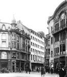 Die Eisengasse, rechts das Warenhaus GLOBUS, in der Mitte das Modehaus MERKUR, dann links davon das soeben fertig erbaute Restaurant HELM und an der Ecke ein Zigarrenladen, Foto aus den 30er-Jahre
