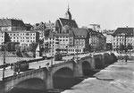 Die Mittlere Brücke mit zwei Trammotorwagen der Linie 6. Blick Richtung Grossbasel: Blaues Haus, Martinskirche, Café Spillmann, Buchhandlung Wepf, Globus, Restaurant Lällekönig, Schifflände, ca. 1947.
