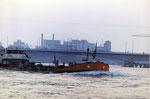 Ein Tankschiff auf dem Rhein, im Hintergrund die neue Johanniterbrücke und der St.Johann-Hafen, 1967