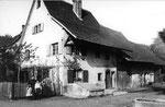 Ein Dorfhaus in Kleinhüningen vor dem Abbruch, im Hintergund links die neuen Silos