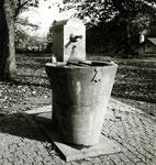 Ein Basler Brunnen auf dem Freidhof am Hörnli mit angekettetem eisernen Trinkbecher, 1958