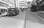 Ein Trammotorwagen der Serie Be 2/2 der Linie 7 auf dem Wartegleis und ein Bus Linie 36 in der Spiegelgasse die Haltestelle Schifflände anfahrend, 1969