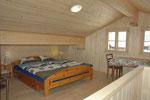 Gibelzimmer mit Doppelbett und zwei Einzelbetten und Aufenthaltsbereich