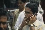 Mittelständischer Inder mit Handy, Uhr und Zigarette