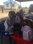 Am Mittagstisch und im Hintergrund das erste Njumba Mteja (Klienten Haus)