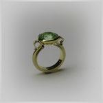 Ring in Gold mit einer antik anmutenden Form. Die zwei rund auslaufenden Ornamente halten einen hell scheinenden Smaragd.